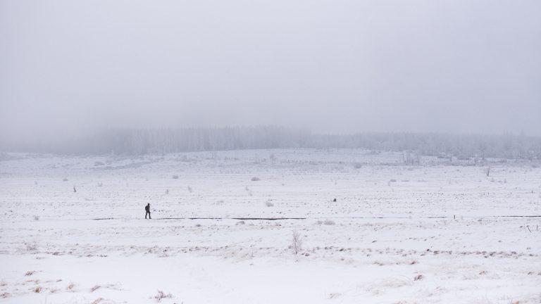 Man stapt alleen door besneeuwd landschap
