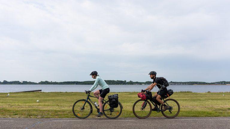 Fietsers fietsen langs het water aan het Veerse Meer