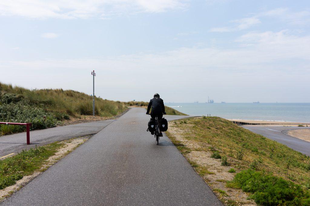 Fietser fiets langs de kustlijn in Breskens